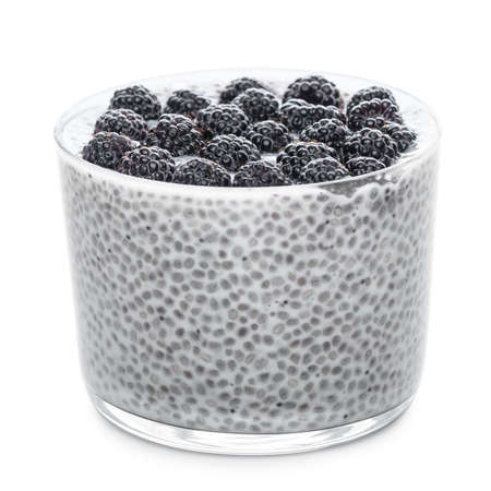 Chia seeds pudding with black raspberries in glass isolated on white Stock Photo