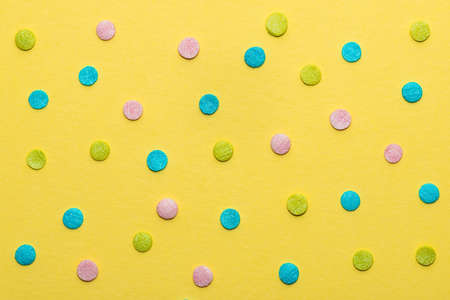 colorful round sprinkles over yellow background, decoration for festive Valentines day, birthday, holiday and party time 版權商用圖片