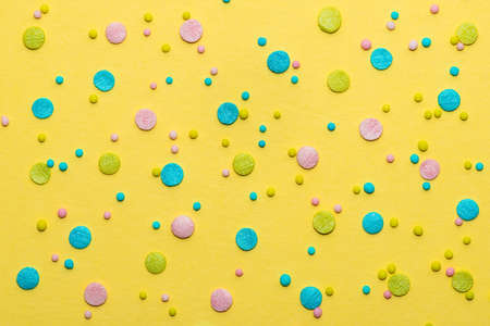 colorful round sprinkles over yellow background, decoration for cake and baker