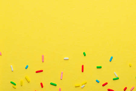 colorful sprinkles over yellow background, decoration for festive Valentines day, birthday, holiday and party time, copy space