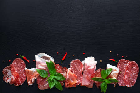 flat lay of set antipasti with sliced salami, prosciutto, ham, basil and dry peppers on black slate background, copy space