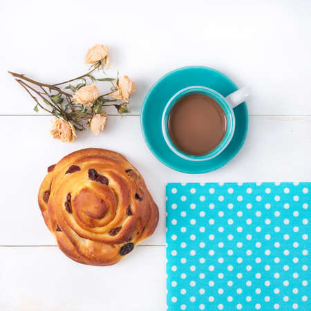 Blue cup of coffee on a saucer, blue napkin in white pea, cake with raisins and pressed a bouquet of roses on a white wooden surface.