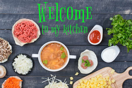 Soup with meatballs, vegetables and beef for its preparation and sign Welcome to me kitchen. Top view.