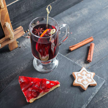 convivial: Mulled wine with strawberry pie and Christmas cookies on the wooden background Stock Photo