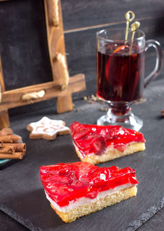 Pieces of cake with a strawberry filling and a souffle and Mulled wine, cinnamon sticks and christmas cookies for decoration.