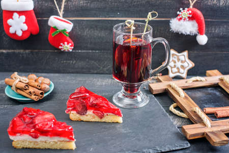 convivial: Mulled wine and strawberries cakes. Xmas style. Wooden background.