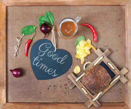 good times: A board Good Times in the form of heart, beer and snack on plywood background Stock Photo