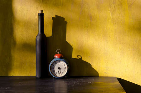 stiil-life with black bottle and old clock on yellow background photo