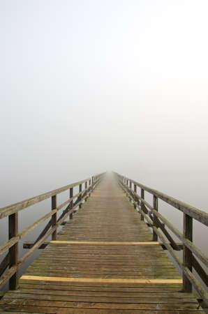 wooden bridge on lake and early morning mist Stock Photo - 12442317