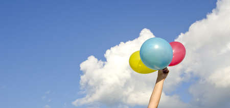 girls hand holding three colorful balloons and cloudy sky photo