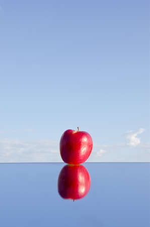 refelction: one red apple with refelction on mirror and sky Stock Photo