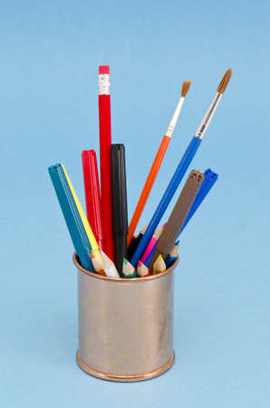various brushes and pencils in the brass vase