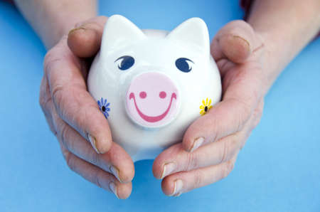 money piggy bank in the old woman hands photo