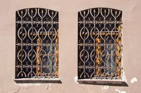 grate: Due vecchie finestre con grigliati metallici ornamentali