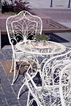 white painted metal cafe furniture in the city street photo