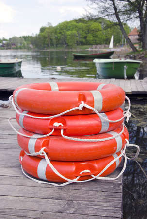 group new red life buoy on lake wooden bridge photo