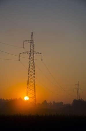 summer sunrise landscape with sun and utility pole photo