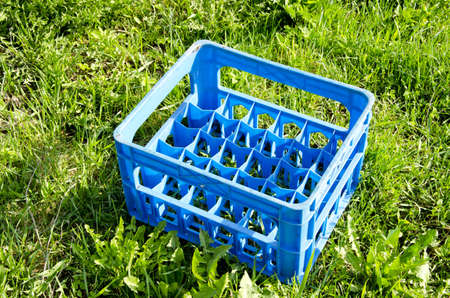 beer bottle empty plastic blue crate on grass photo