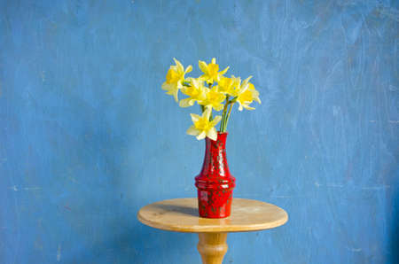 red vase with spring fresh narcissus on table photo