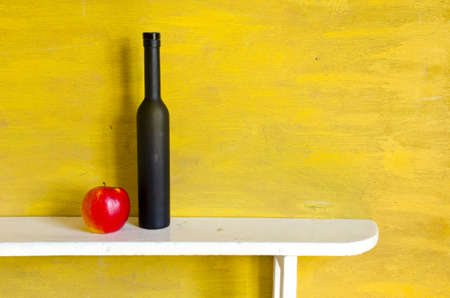 still-life with black bottle and red apple Stock Photo