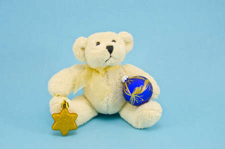 white teddy bear with christmas toys on azure background photo