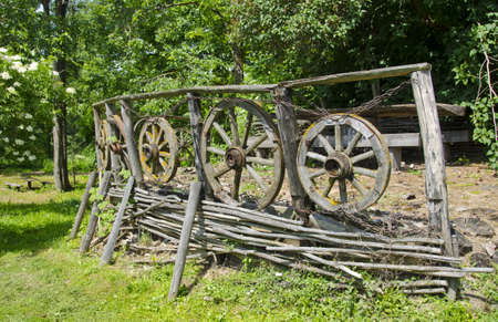 vintage wooden fence with carriage wheels in farm Stock Photo - 17474176
