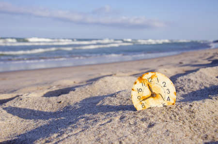 time and sea concept.ocean landscape with old rusted clock dial on sand