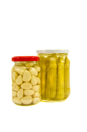 pickled garlic and corn cobs in glass jar isolated on white Stock Photo