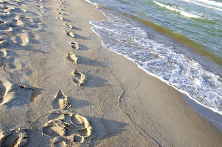 Footprints in wet morning sand of beach and sea vawes Stock Photo