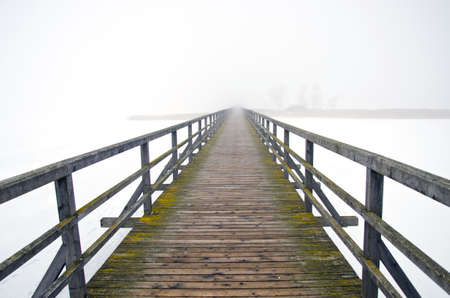 old wooden bridge in winter and mystery morning fog Stock Photo - 18211086