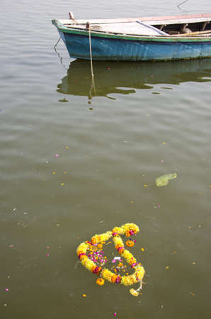 ritual flowers and boat in sacred Ganges river, Varanasi,India photo