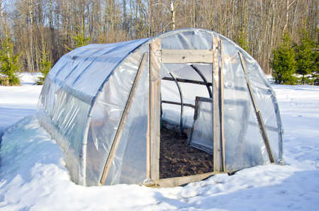 polythene: primitive handmade polythene greenhouse for vegetable  in winter time on snow Stock Photo