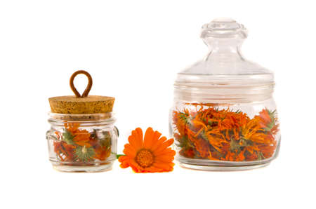 anoint: dry medical herbs calendula in glass jars isolated on white
