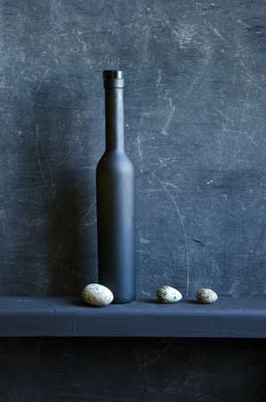 black still-life with bottle and three bird eggs photo