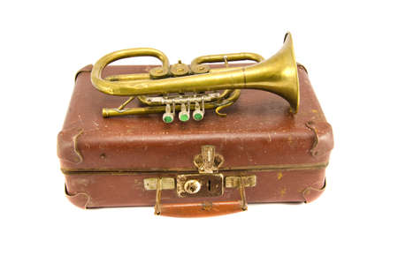old brown suitcase for traveling and vintage brass musical instrument. Isolated objects Stockfoto