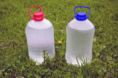 two plastic bottle with cold water on summer garden grass