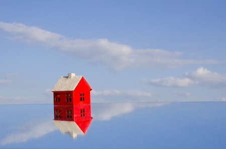 red beautiful house symbol model on mirror and sky Stock Photo