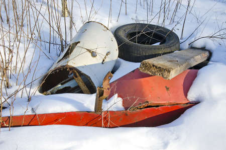 metal and rubber pollution on winter snow. Rubbish in nature photo