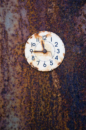 rusted ancient clock face on metal tin background. Time concept photo
