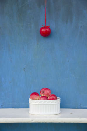 hanging red apple on string and white vase with fruits. Healthy life concept photo