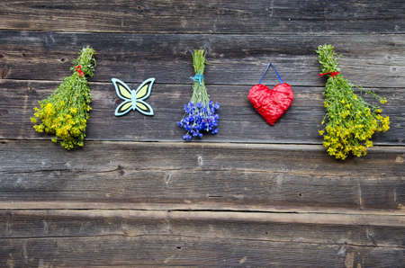 hanging medical herb bunch and red heart on wooden farm wall. Healthy lifestyle concept Stock Photo