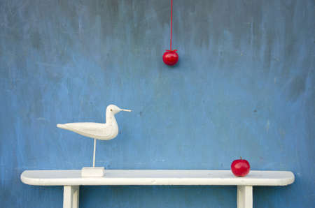 still-life with two red apple and white bird sculpture on shelf photo
