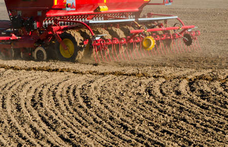 agriculture machinery: new agriculture cereal grain seeder machinery working on farm field. Grain sowing concept