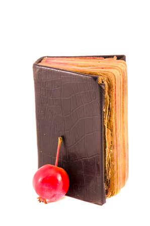 old used christianity prayer book Bible with red apple isolated on white background photo