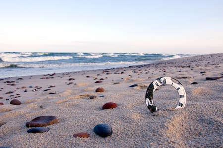 analog aged clock face on sea beach sand. Time concept photo