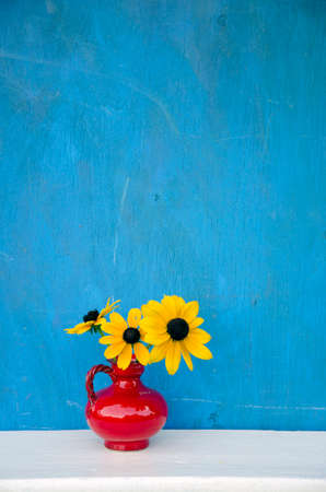 beautiful red vase with yellow flowers on blue background photo