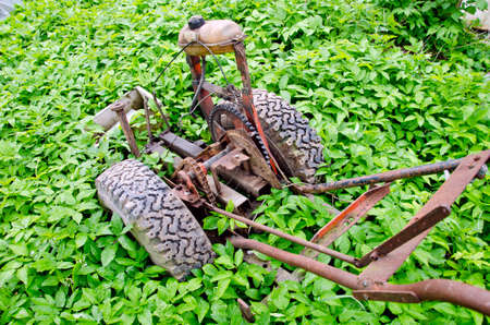 the plough: old broken motor plough in farm spring garden. Agriculture equipment Stock Photo