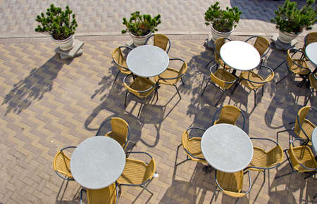table and chairs in summer city street cafe on pavement Stock Photo