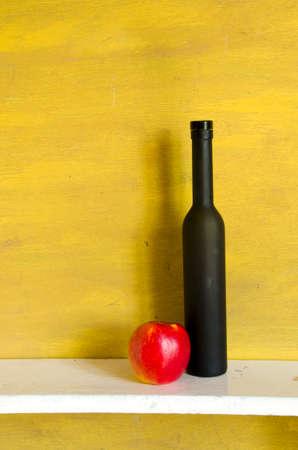 stil: black wine bottle and red apple on white wooden shelf