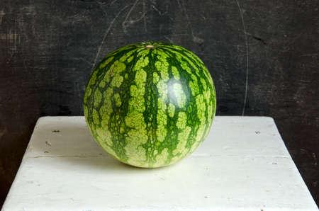 one fresh watermelon on white wooden seat Stock Photo